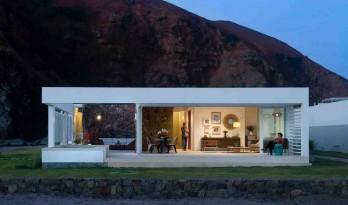 红山石墙上生长出的白色住宅:隆达海边度假别墅