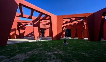 来自火红色的热烈暴击:角形网格梁架遮荫下的校园 / Sanjay Puri