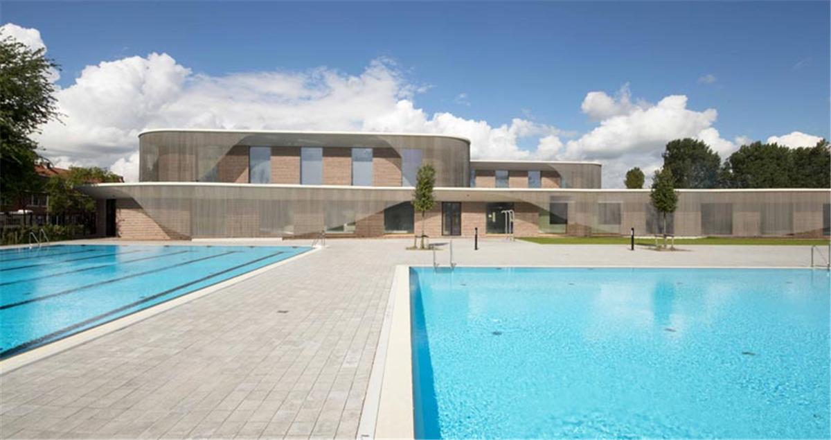建筑位于阿姆斯特丹北部,由當地事務所de architekten cie設計。Noorderparkbad游泳館是一幢獨立的建筑,造型輕盈,呈歡迎的姿態對外敞開。游泳池實現了建筑和景觀的完美過渡,不同于傳統的大型游泳館,Noorderparkbad更像是坐落在公園中的展覽館。柔和的造型和彎曲的幕簾把建筑和景觀區分開來,建筑上層體量的退后處理,使游泳館與公園和住宅區更加契合,同時,也有利于建筑內部的采光。  波浪形的幕簾設計使人眼前一亮,它作為設計的重點,傳達了游泳池與水的密切聯系。在雨天,水流像瀑布一樣沿