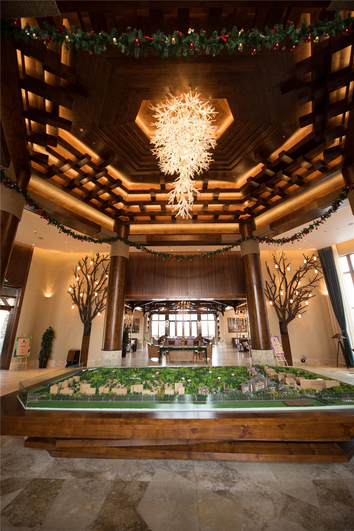 长白山红松溪谷酒店位于长白山旅客集散中心,按五星级高端精品温泉度假酒店设计。酒店充分融入周边环境,巧妙地将独特的长白山元素(尤其是水、火、冰、岩、鹿、皮、雾、林八种经典长白山元素)及萨满文化融入设计之中,从而让客人享受到长白山的文化精髓及独特气候。   作为典型,长白山脉当地的木材被运用于酒店大范围的装饰设计,比如照明设备和墙面的装饰。这不仅强调了酒店的主题,体现了长白山的独特元素,同时也节省了材料的运输成本。  木质材料的选择有木饰面、木地板、新实木、老实木四种方向。木饰面和木地板难以体现与主题所呼应